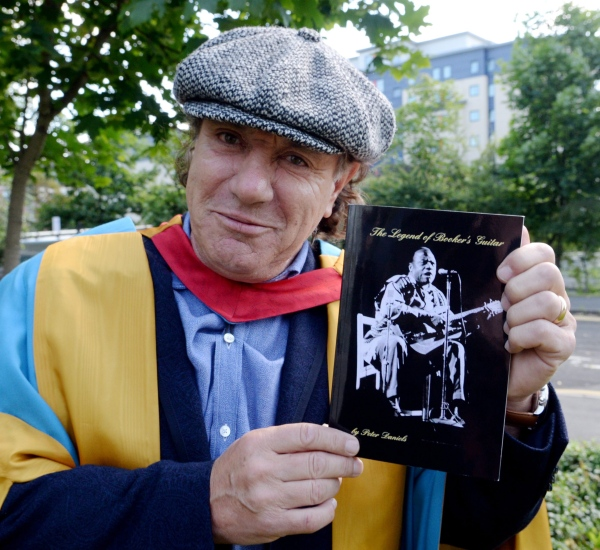 "AC/DC star Brian Johnson with his copy of The Legend of Booker's Guitar. ""Buy this book,"" says Brian. ""It's cheap and it's fun!"""
